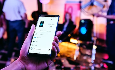Ospite del party che usa l'app Sony | Music Center dallo smartphone