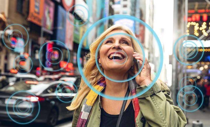 Donna in una strada affollata che ascolta con Voice Zoom 2