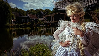 Frank-Doorhof-sony-alpha-7RIII-bride-standing-in-front-of-lake-looking-pensive