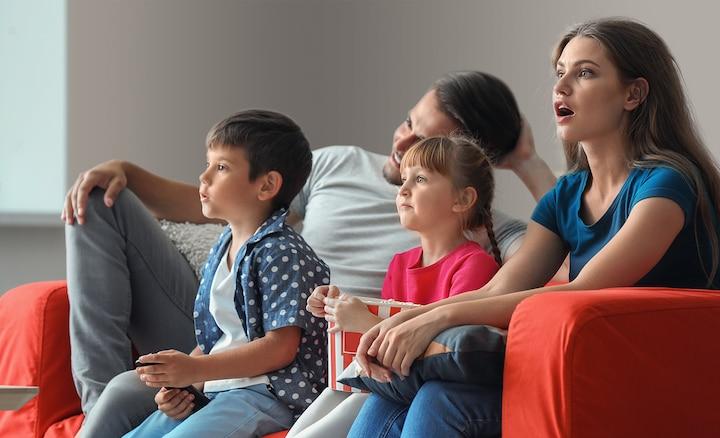 Quattro persone sedute su un divano rosso che guardano la TV e mangiano popcorn