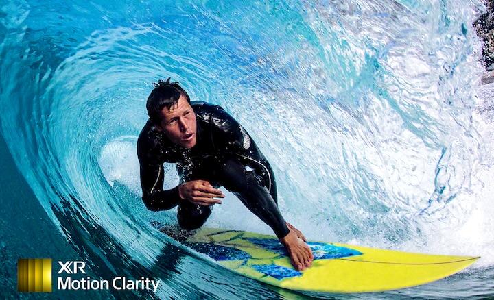 Immagine dettagliata senza sfocatura di un surfista su un onda